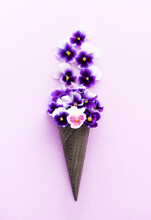 Healthy Life Concept. Edible Flowers Pansies Viola In A Waffle Cone On Lilac Background, Flat Lay
