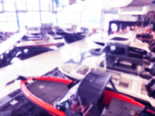 Blurred Background With Fishing Motor Boat In The Dealership Store. Blur Motorboat Showroom Background. Bokeh Light