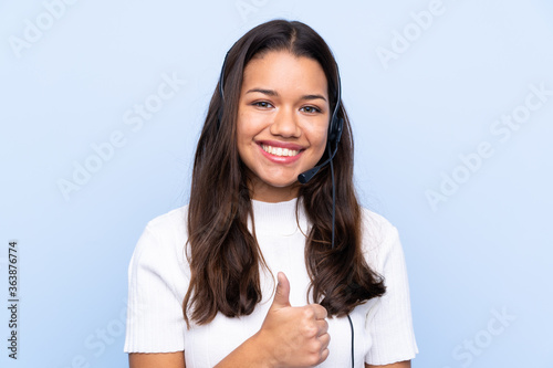 Young telemarketer Colombian woman over isolated blue background giving a thumbs Canvas-taulu