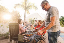 Man Cooking Food On Barbecue Grill While Family Enjoying Meal In Background At Yard