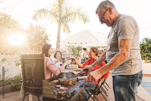 Valokuva Man Cooking Food On Barbecue Grill While Family Enjoying Meal In Background At Y
