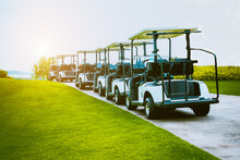 Golf Cart On Golf Course, Parking On Fairway. Equipment And Golf Club Bag Are Put In Ready For Golfer To Player In Field With Sunlight Rays Background