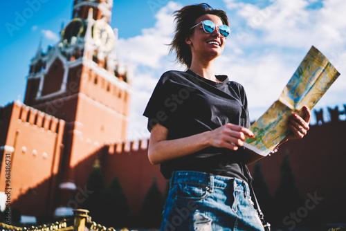 Fotografiet Cute cheerful female blogger enjoying vacation holidays during strolling at sunny urban setting