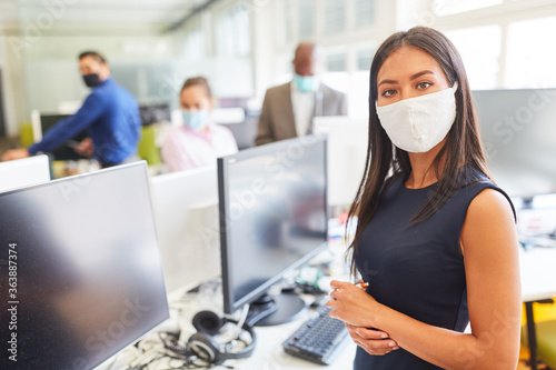 Young businesswoman with face mask as protection