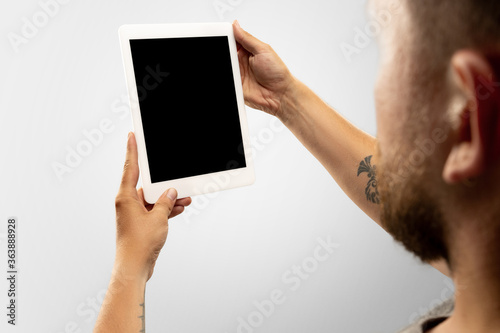 Fotografia Close up male hands holding tablet with blank screen during online watching of popular sport matches, championships