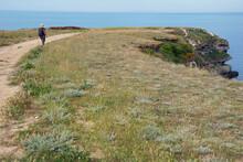 Black Sea Region. Cape Tarkhankut. A Woman In A Hat Is Walking Along The Road.