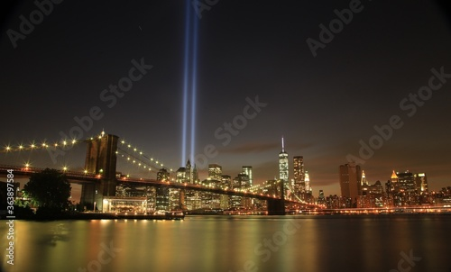 Fotografering Illuminated Brooklyn Bridge Over East River By Modern City With Light Beams At N
