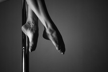 Low Section Of Woman Dancing On Pole Against Wall