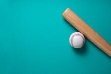 Baseball And Baseball Bat On Green Table Background, Close Up