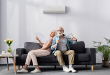 Senior Woman Holding Fan While...