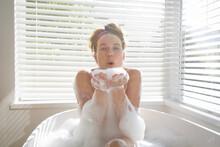 Woman Blowing Soap Bubbles In ...