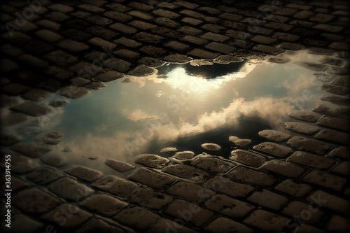 High Angle View Of Clouds Reflection In Puddle On Cobblestone Street Wallpaper Mural