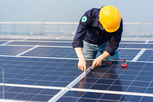 Obraz Electrician engineer with a helmet yellow is inspection the solar panel on the roof of the building.  - fototapety do salonu