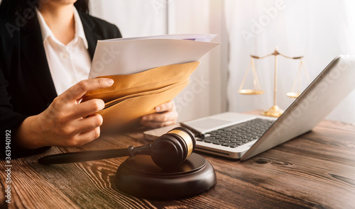 Foto Business and lawyers discussing contract papers with brass scale on desk in office