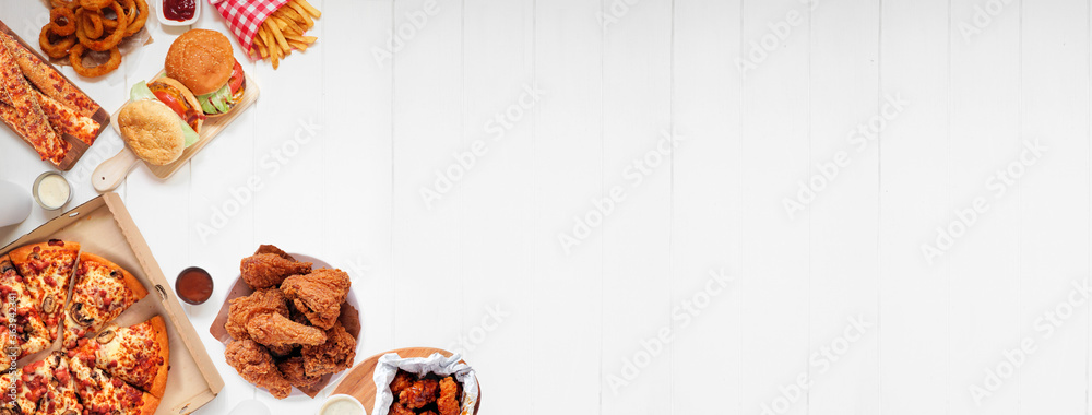 Fototapeta Selection of take out and fast foods. Corner border banner. Pizza, hamburgers, fried chicken and sides.  Top down view on a white wood background with copy space.