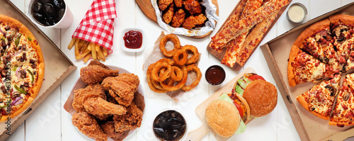 Table scene of assorted take out or delivery foods. Pizza, hamburgers, fried chicken and sides. Top down view on a white wood banner background. © Jenifoto