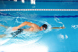 Fototapeta Tulipany - Man swimmer is swimming in the pool. Freestyle stroke, front crawl stroke. Swimming in blue pool, side view. breathing technique during swimming