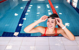 Fototapeta Tulipany - Positive woman swimmer adjusting her swimming goggles, at a swimming pool. Swimmer in a pool