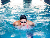 Fototapeta Tulipany - Swimming in motion. Swimmer demonstrates the butterfly stroke technique. Training different swimming styles. Soft focus in motion