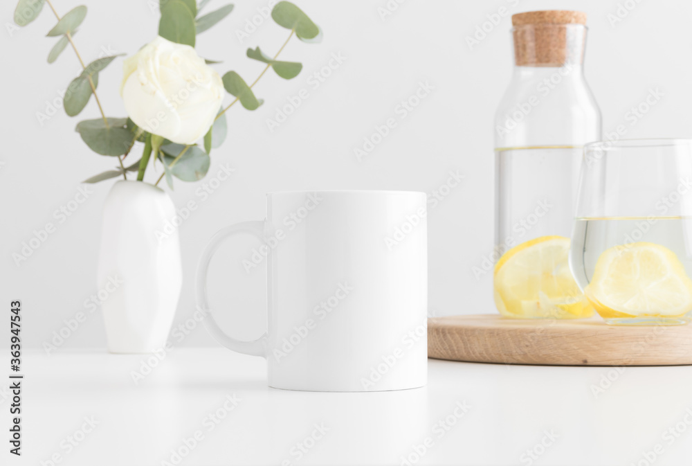 Fototapeta White mug mockup with flowers in a vase, glass and a bottle on a white table.