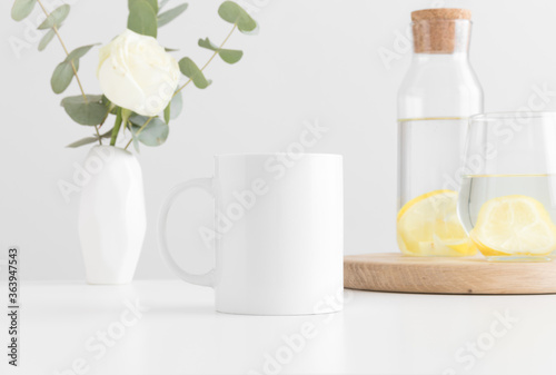 Fototapeta White mug mockup with flowers in a vase, glass and a bottle on a white table. obraz