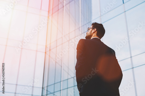 Photographie Back view of serious businessman in eye glasses looking on copy space while stan