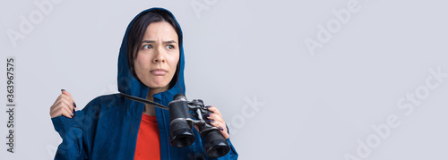 Fotografie, Obraz A tourist girl in a blue raincoat holds binoculars in her hands and looks into the distance, spies