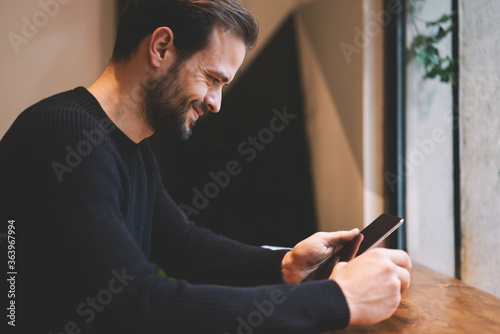 Cheerful handsome bearded employer reading funny stories in social networks on touch pad using 4G connection Wallpaper Mural