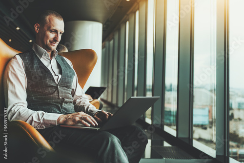 Obraz A cheerful successful businessman is working on his laptop while sitting on an armchair indoors of a luxurious office interior, with a window and a copy space zone on the left for an advertising text - fototapety do salonu