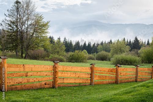 Fototapeta Widok na zamglone góry zza drewnianego ogrodzenia obraz