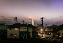 Fog And Mist After Dusk Move Over Residential Neighborhood With Tall Apartment Tower In Background