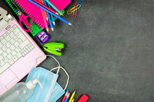 School Supplies And Coronavirus Prevention Items. Side Border On A Chalkboard Background. Back To School During Pandemic Concept.