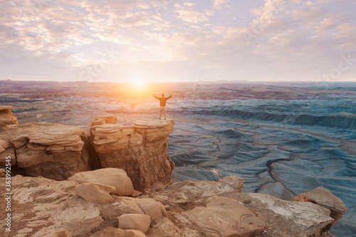 Fotografija Man stands triumphant with his hands outstretched in victory while standing on a