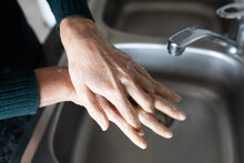 Mid Section Of Woman Washing Her Hands In The Sink