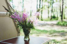 Bouquet Of Forest Flowers In Vase On Table Near Camper In The Forest. Local Tourism Concept