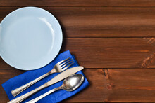 Empty Plate And Cutlery With Blue Towel On Wooden Background. Blue Plate, Fork, Knife, Spoon.Flat Lay, Top View.