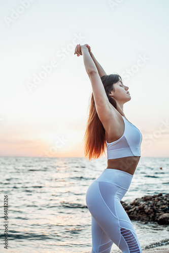Fotografia Side view of young woman standing in Warrior yoga position on sandy beach