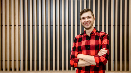 Young man carpenter in checkered shirt