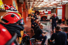 Closeup Of Firefighter Sitting And Listening Boss Who Is Talking About Tactic How They Gonna Extinguish The Fire. Fire Brigade Interior. Closeup Of Protective Suit And Helmet.