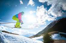 Girl Skier In Flight After Jumping From A Kicker In The Spring Against The Backdrop Of Mountains And Blue Sky. Close-up Wide Angle. The Concept Of Closing The Ski Season And Skiing In Spring