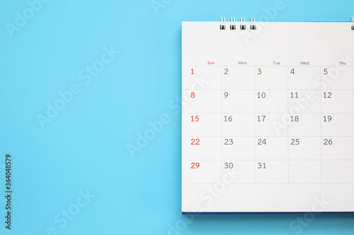 Fototapeta calendar page close up on blue background business planning appointment meeting concept obraz