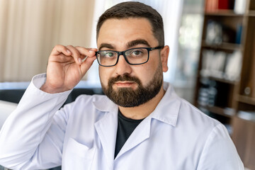 Portrait of a bearded doctor looking at camera. Doctor in glasses in office.