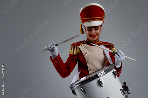 Fototapeta cheerful young woman in a red cap and uniform plays a drum. obraz