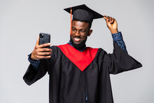 Young African Man Graduate In Gown And Cap Take Selfie Isolated Over White Background