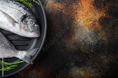 Fotografie, Obraz Raw sea bream or dorado raw fish on grill pan with ingredients on old metall dark background, top view with space for text