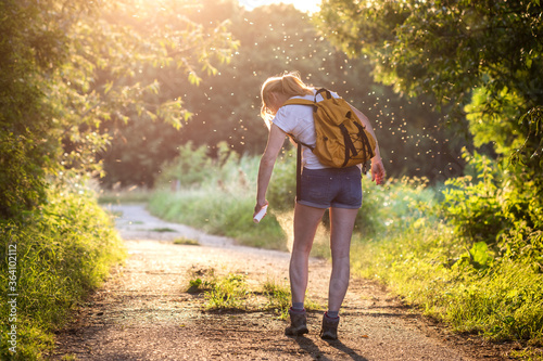 Fotografija Woman applying insect repellent against mosquito and tick on her leg during hike in nature