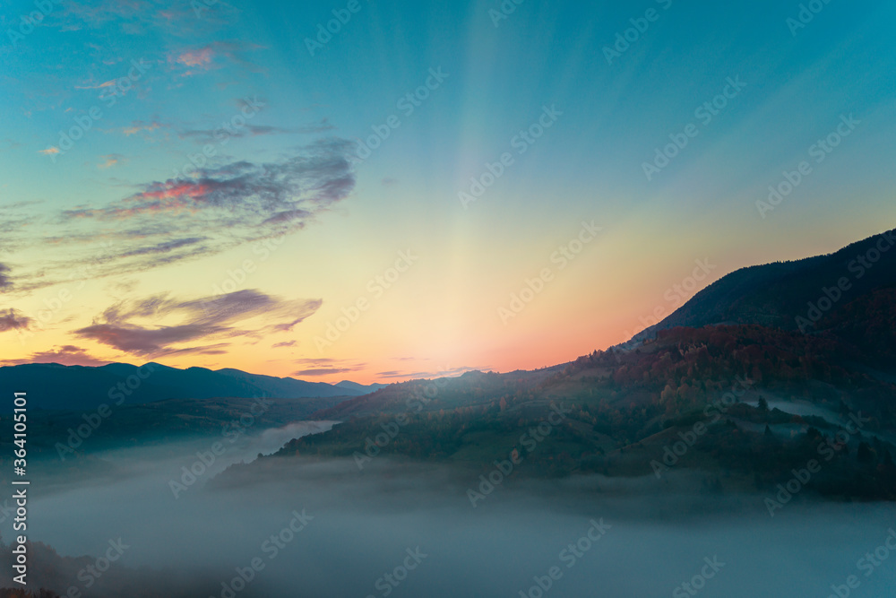 Fototapeta View of beautiful landscape in hillside meadow with bright rising sun on background. Morning sun illuminating rolling hills with light rays. Concept of nature and environment.