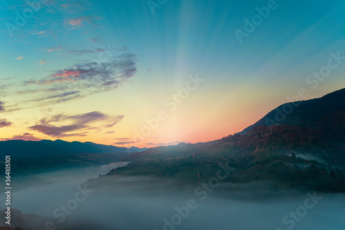 Fototapeta View of beautiful landscape in hillside meadow with bright rising sun on background. Morning sun illuminating rolling hills with light rays. Concept of nature and environment. obraz