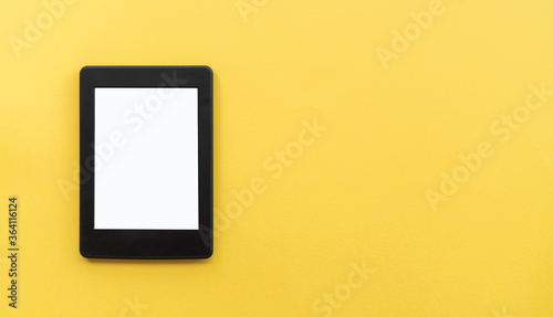 A modern black electronic book with a white blank empty screen on yellow backgro Canvas Print