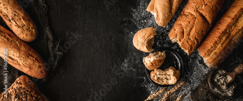 Fototapeta Freshly bread baguettes and buns on black slate background with wheat spikelets, sackcloth. Pastries and bakery, top view, wide composition obraz